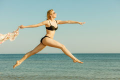 Woman wearing bikini playing, jumping near sea Royalty Free Stock Image