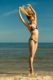Woman wearing bikini playing with water in sea Stock Images