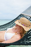 Woman Wearing Bikini And Sun Hat Relaxing In Beach Hammock Royalty Free Stock Images