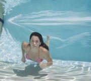 Woman wearing a bikini swimsuit holding her breathe underwater. Stock Photography