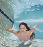 Woman wearing a bikini swimsuit holding her breathe underwater. Stock Photos