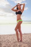 Woman wearing bikini walking on beach Stock Images