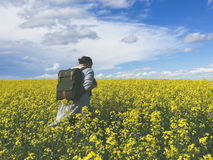Woman Wearing Black Backpack Walking on a Flower Field Stock Photography