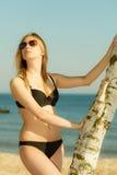 Woman wearing black bikini posing next to tree Royalty Free Stock Images