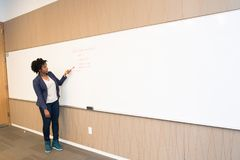 Woman Wearing Black Blazer Holding Pen Pointing White Marker Board Stock Images