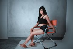 Woman Wearing Black Camisole and Short Shorts Sitting on Orange Director's Chair stock image