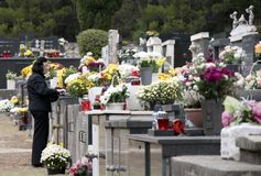 Woman wearing black at the cemetery full of flowers and candels stock image