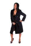 Woman wearing black coat. Full length portrait of an African American woman wearing a black coat, she has one hand on her hip and is looking to the side Stock Photos