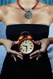 Woman wearing black dress. And many coral rings holds a red vintage alarm clock Stock Image