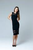 Woman wearing black dress. Fashionable beautiful woman wearing black dress on gray background Stock Images