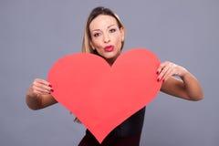 Woman wearing black dress holding big heart sign love symbol Royalty Free Stock Image