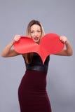 Woman wearing black dress holding big heart sign love symbol Stock Photo