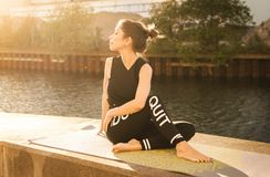 Woman Wearing Black Fitness Outfit Performs Yoga Near Body of Water royalty free stock images