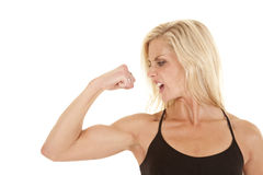 Woman wearing black flex arm mad. A woman looking at her arm while she is flexing with a upset expression on her face Stock Photo