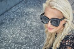 Woman Wearing Black Framed Wayfarer Style Sunglasses and Black Floral Top Near Gray Concrete Pavement Stock Photography