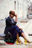 Woman Wearing Black and Grey Tattersall Blazer and Multicolored Plaid Skirt With Black Mesh Stocking and Yellow Chunky Heeled Sand Royalty Free Stock Photo