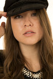 Woman wearing black hat looking at camera somber look. A brunette woman with a stoic look wearing a black hat Stock Photo