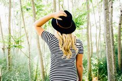 Woman Wearing Black Hat and Striped Shirt in Trees Touching Hat in Daytime Royalty Free Stock Photo