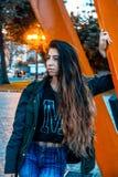 Woman Wearing Black Jacket Leaning on Orange Metal stock images