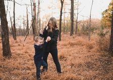 Woman Wearing Black Jacket Playing With Young Boy Stock Image