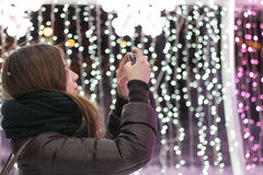 Woman Wearing Black Jacket Taking a Picture of Lights Stock Image