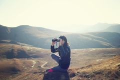 Woman Wearing Black Jacket Using Binoculars Sitting on Mountain Royalty Free Stock Images