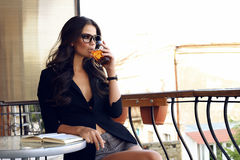 Woman wearing black jacket,watch and  glasses, sitting at cafe and drinking tea Royalty Free Stock Photos