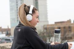 Woman Wearing Black Jacket With White Headphones Stock Photos