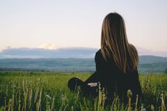 Woman Wearing Black Long Sleeved Shirt Sitting on Green Grass Field Near Mountain Under Cloudy Sky stock photography