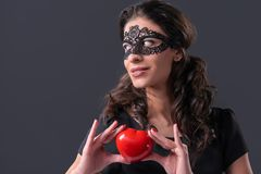 Woman wearing black mask holding heart shape Royalty Free Stock Photos