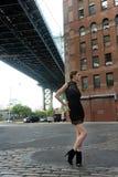 Woman wearing black minidress standing under Manhattan Bridge Stock Photography