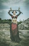 Woman Wearing Black and Red Dress Holding Sword Standing on Rock Surface during Day Time Royalty Free Stock Photo