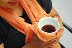 Woman wearing a black shirt is drinking coffee. Royalty Free Stock Image