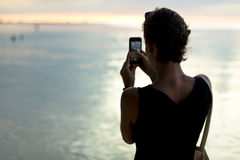 Woman Wearing Black Sleeveless Shirt Taking a Picture of Beach Royalty Free Stock Images