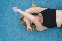 Woman Wearing Black Sports Brassiered Lying on Teal Surface While Covering Her Face With Her Arms royalty free stock images