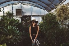 Woman Wearing Black Tank Dress and Hat in Greenhouse Stock Images
