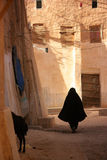 Woman wearing black veil. Woman in traditional clothing walking down the dusty street Royalty Free Stock Photography