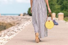 Woman Wearing Black and White Striped Maxi Skirt Holding Brown Bag stock photography