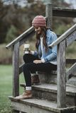 Woman Wearing a Blue Denim Jacket Holding a Cup of Coffee Royalty Free Stock Photography