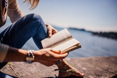Woman Wearing Blue Denim Jeans Holding Book Sitting on Gray Concrete at Daytime Stock Photography