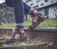Woman Wearing Blue Denim Skinny Pants and Black Pink Floral High Top Shoes Walking Down Train Track during Daytime Royalty Free Stock Photo