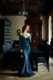 Woman wearing blue dress. Pretty Woman with red curly hair wearing vintage blue dress Royalty Free Stock Photo