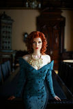 Woman wearing blue dress. Pretty Woman with red curly hair wearing vintage blue dress Stock Image