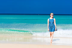 Woman wearing a blue dress walking on a beach Stock Images