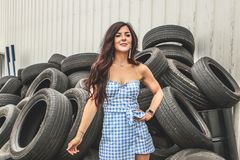 Woman Wearing Blue Flannel Dress Standing in Front Car Tires royalty free stock photo