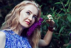 Woman Wearing Blue Floral Sleeveless Dress Smelling Violet Flower Stock Photos
