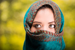 Woman wearing blue, grey and brown coloured scarf covering face only revealing beautiful green eyes, garden background Stock Photo