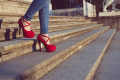 Woman wearing blue jeans and red high heel shoes in old town. The women wear high heels walk on stairs. Sexy legs in red high heel Stock Photo