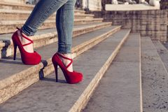 Woman wearing blue jeans and red high heel shoes in old town. The women wear high heels walk on stairs. legs in red high heel royalty free stock images