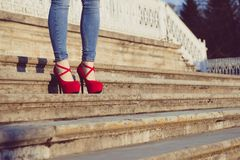 Woman wearing blue jeans and red high heel shoes in old town. The women wear high heels walk on stairs. Sexy legs in red high heel. Detail close up of woman legs Stock Photography